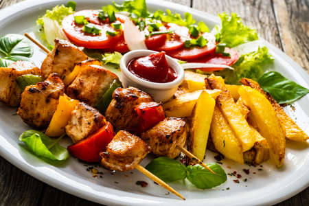 Photo for Skewers - grilled meat with French fries and fresh vegetables on wooden background - Royalty Free Image