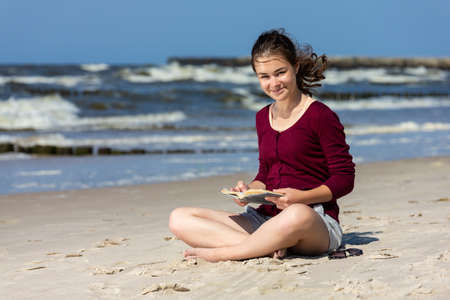 Photo for Teenage girl reading book sitting on beach - Royalty Free Image