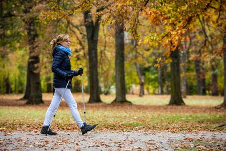 Photo pour Nordic walking - middle-age woman training in city park - image libre de droit