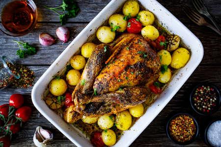 Photo pour Whole roast chicken with vegetables on wooden table - image libre de droit