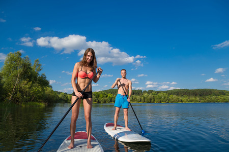 Young attractive couple on stand up paddle board in the lake, SUP