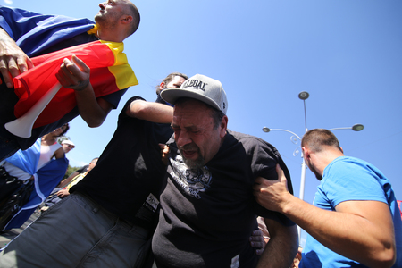 Photo pour BUCHAREST, ROMANIA - August 10, 2018: People are hurt after clashing with riot police during an anti-government protest calling on the left-wing government to resign and an early election, in Bucharest, Romania, Friday, Aug. 10, 2018. - image libre de droit