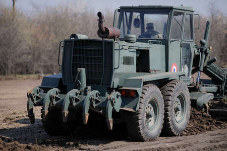 Photo pour Otopeni, Romania - February 19, 2020: Heavy machinery of the Romanian Army level the ground for a campaign mobile hospital (ROL 2) to treat Covid-19 patients. - image libre de droit