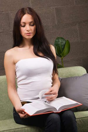 Beautiful brunette reading a book in home interiorの写真素材