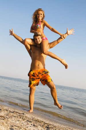Beautiful young couple having fun on the seaside