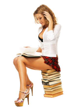 Sexy student girl with sitting on a stack of books against white background