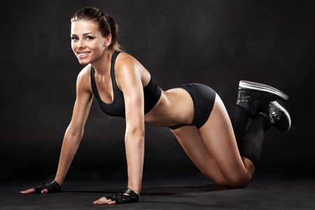 Foto de Young fit woman in sports outfit, doing push-ups - Imagen libre de derechos