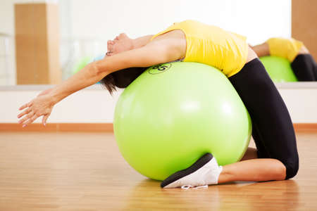 Woman doing fitness in a gym on a ball