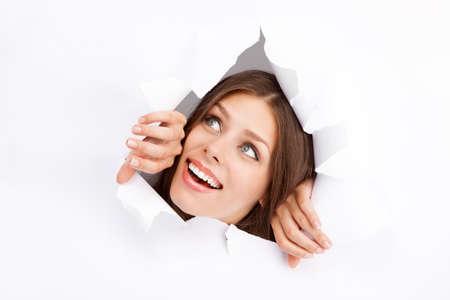 Young woman breaking through a paper sheet.
