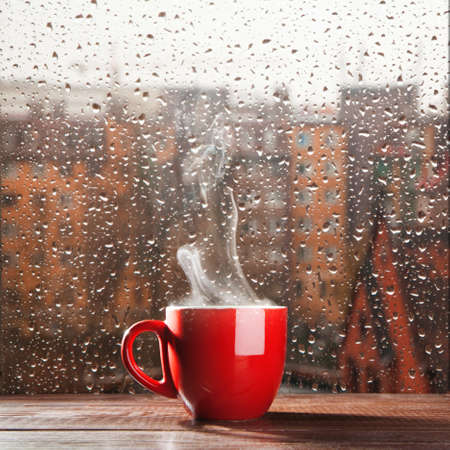 Steaming coffee cup on a rainy day window の写真素材