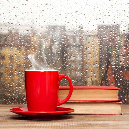 Steaming coffee cup on a rainy day window backgroundの写真素材