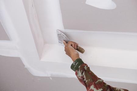 Photo pour hand of worker using gypsum plaster ceiling joints at construction site - image libre de droit