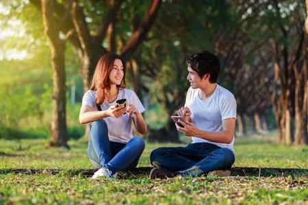 Foto de couple using mobile phone and talking in the park - Imagen libre de derechos