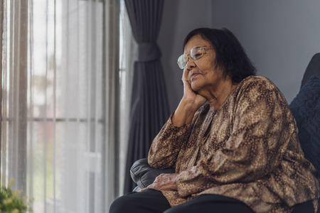old lonely woman sitting on sofa in living room at home