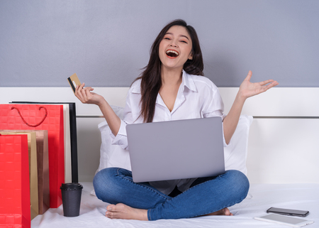 Photo pour happy woman using laptop computer for online shopping with credit card on a bed - image libre de droit