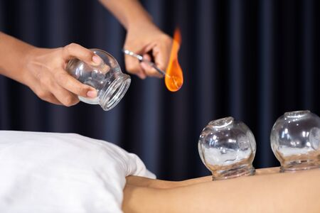Photo for close up glass cup with fire for cupping treatment on female back - Royalty Free Image