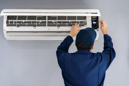 Photo for Electrician with screwdriver repairing the air conditioner indoors - Royalty Free Image