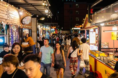 Bangkok, Thailand - Dec 6 ,2019 : Tourist and locals walking and shopping at Rachada Night train market (Talad Rot Fai). market with plenty of shops with colorful canvas roofs at night in Bangkok, Thailand