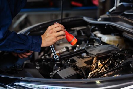 Photo pour male mechanic holding and shining flashlight to checking a car engine problem - image libre de droit