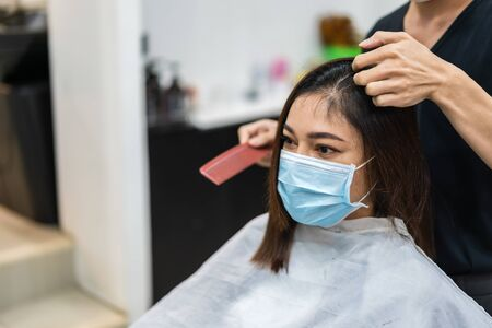 Foto für hairdresser cutting the hair to a female client, people must be wering medical mask to protection coronavirus (covid-19) pandemic. new normal concepts - Lizenzfreies Bild