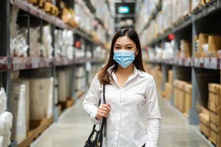 Photo for woman wearing medical mask in the warehouse store during coronavirus (covid-19) pandemic. - Royalty Free Image