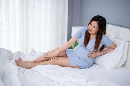 Photo pour pregnant woman massaging leg on a bed, painful muscle, sprain or cramp ache - image libre de droit