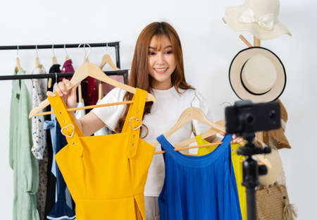 Photo pour young woman selling clothes and accessories online by smartphone live streaming, business online e-commerce at home - image libre de droit