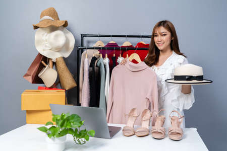 Photo pour young woman selling clothes and accessories online live streaming, business online e-commerce at home - image libre de droit