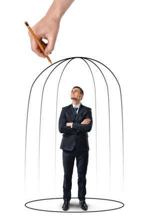Businessman with his arms folded standing in a hand drawn cage isolated on white background. Business staff. Despair and misfortune. Office clothes. Helpless situation.