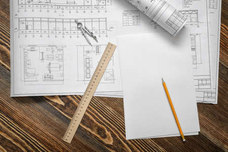 Open blueprints on wooden table background with a pencil, a ruler and compasses lying beside.