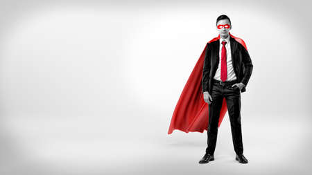 A self-assured businessman in a red cape and a mask standing with a hand in his pocket on white background.