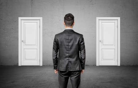 Foto de A businessman with his back turned stands between two identical closed white doors. - Imagen libre de derechos
