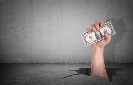 Foto de A large male hand striking out of a deep cracked hole in a cement floor to catch a dollar bill. - Imagen libre de derechos