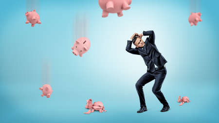 A businessman hides his head from many piggy banks that fall down and crack at the floor.