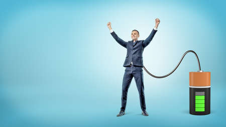 Photo pour A happy businessman with raised hands is connected to a large battery charging him. - image libre de droit