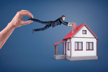 Photo pour A businessman tries to hold onto a chimney of a small house while he is dragged away by a giant hand. - image libre de droit
