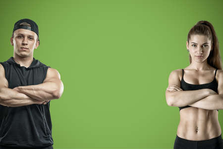 Foto de A young muscular woman and a fit man stand on a green background. - Imagen libre de derechos