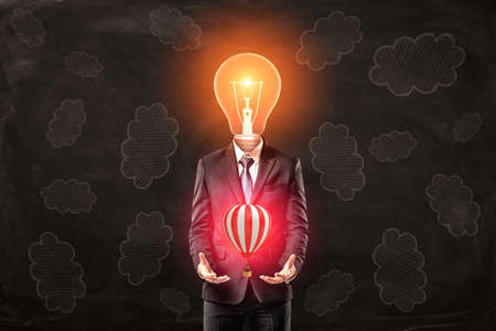Photo for Man in suit with lightbulb instead head, levitating small hot-air balloon above his palms, standing against black wall with clouds pattern on it - Royalty Free Image