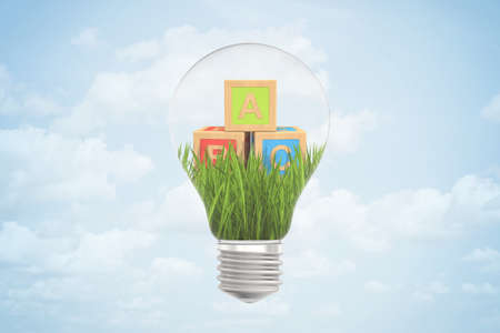 Foto de 3d closeup rendering of lightbulb with three ABC blocks lying on green grass inside bulb against blue sky with clouds. - Imagen libre de derechos