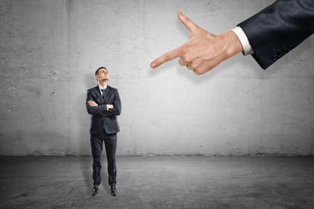 Photo for Front full length view of little businessman standing and looking up at huge hand pointing index finger at him. - Royalty Free Image