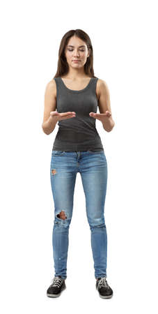 Photo pour Front view of young woman in gray top and blue jeans standing with elbows bent as if holding invisible tablet isolated on white background. - image libre de droit