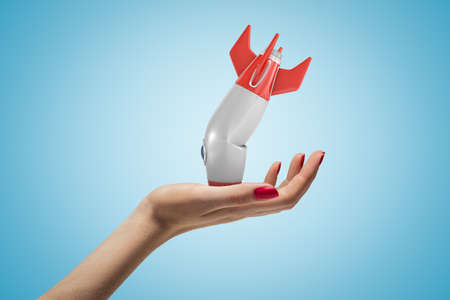 Photo pour Side closeup of womans hand facing up and holding small broken rocket upside down, on light blue gradient background. - image libre de droit