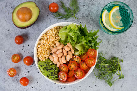 Photo for A plate of fresh salad with white beans, bulgur, cherry tomatoes and avocado, decorated with black sesame seeds with products around the plate. Horizontal photo with copy space, top view - Royalty Free Image