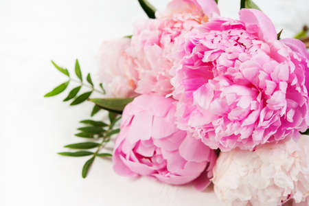 Photo for Close up bouquet of fresh beautiful flowers lies on a white background. Pink peonies lie on the right . Horizontal photo - Royalty Free Image