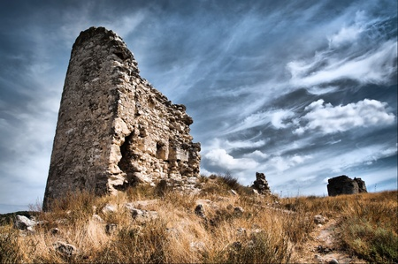 ruined castle stands in a field against sky