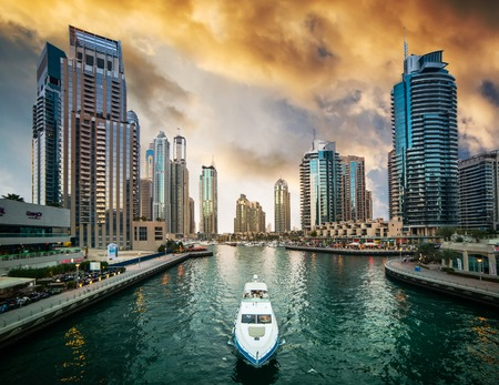 Photo pour Dubai, United Arab Emirates - December 14, 2013: Modern skyscrapers and water channel with boats of Dubai Marina at sunset, United Arab Emirates - image libre de droit