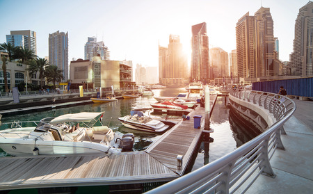 Photo for Panoramic view with modern skyscrapers and water pier of Dubai Marina at sunset, United Arab Emirates - Royalty Free Image