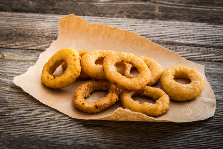 fried onion rings on parchment on a wooden background