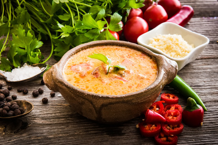 Sope queso with vegetables and spices on a wooden background