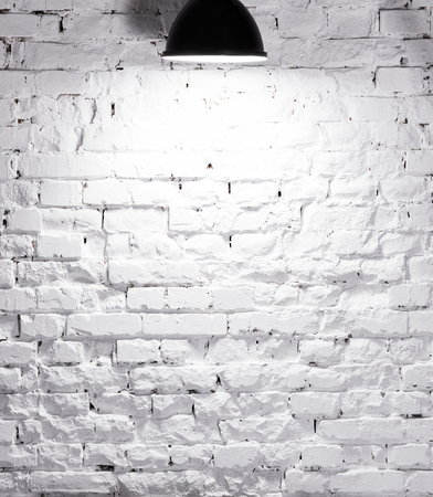 texture of brick whitewashed wall illuminated with lamp on top